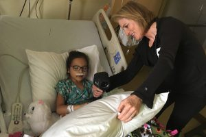 Alterwitz at the hospital with a pediatric patient while the child captures thermal photographs in her hospital room.